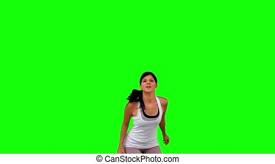 Woman in sportswear leaping on green screen  in slow motion