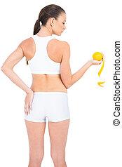 Woman in sportswear standing back to camera holding orange
