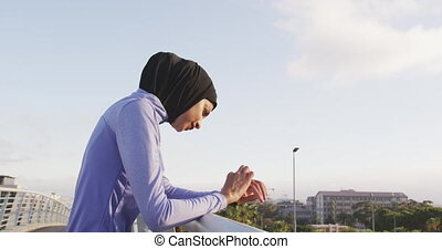 Woman in sportswear wearing hijab - Side view of a mixed-...