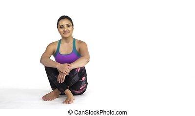 Woman in sportwear sitting on floor showing blank copy space