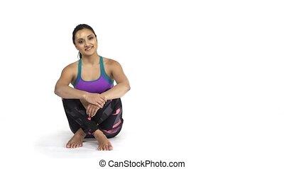 Woman in sportwear sitting on floor showing blank copy space...