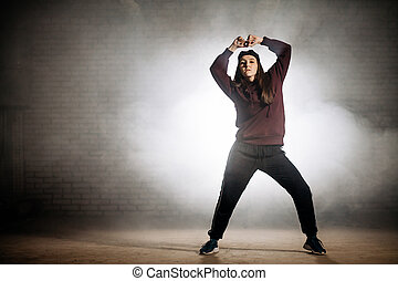 woman in sporty clothers with raised hands posing to the camera on the street