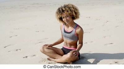 Woman In Sporty Outfit Sits On The Sand