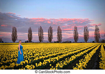 Woman in spring fields meadows with yellow flowers.
