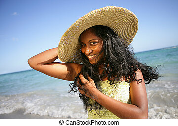 Woman in straw hat having fut at the beach