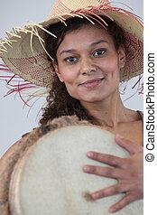 Woman in straw hat holding bongo drum