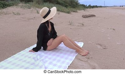 Woman in straw hat on the beach by the sea