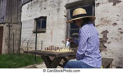 Woman in straw hat relaxing near chess outdoor