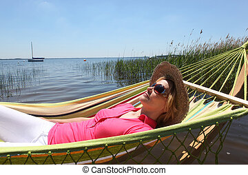 Woman in straw hat relaxing on a hammcock