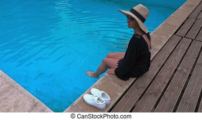 Woman in straw hat relaxing on edge of pool