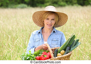 Woman in straw hat with basket of vegetables walking through a field