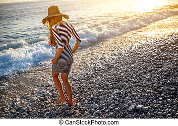 Woman in stripped dress with a hat on the beach - Young and...