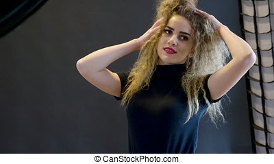 Woman in studio photo session posing on black background