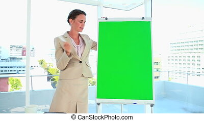 Woman in suit giving a presentation with a board