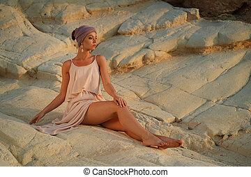 woman in summer dress on the rocks