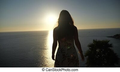 female silhouette raises hands standing on beach edge at sunset slow motion