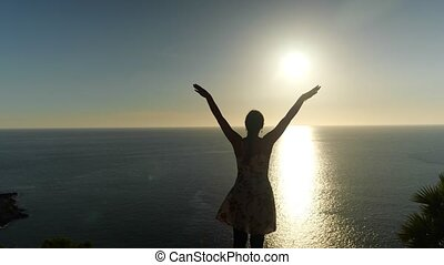 woman in summer dress silhouette raises hands standing on endless ocean beach edge against bright setting sun backside