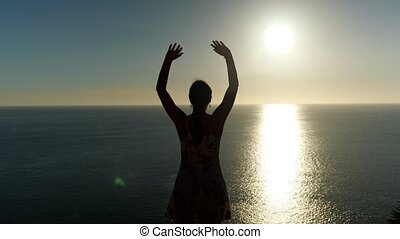 woman in summer dress silhouette stands and raises hands on ocean beach against sunset