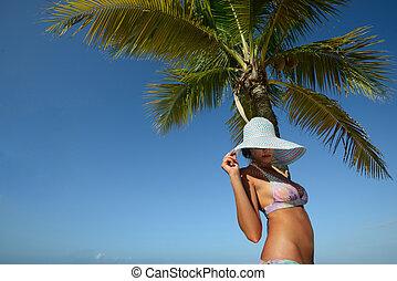 Woman in summer hat sunbathing under a palm tree on a background of blue sky. Island Roatan