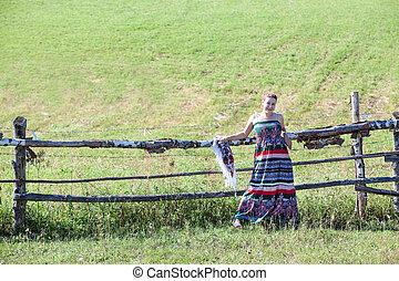 Woman in sundress standing near village fence in field. Copyspace