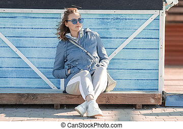woman in sunglasses against the background of a wooden wall