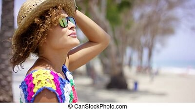 Woman in sunglasses and hat outside looking up