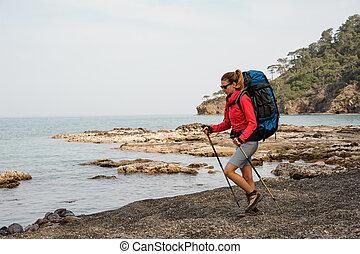 Woman in sunglasses hiking on sea coast
