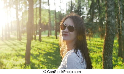 Woman in sunglasses in park looks at the camera