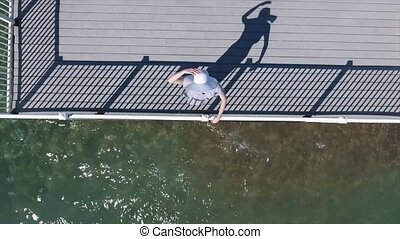 Woman in sunglasses is standing on the wooden pier and looking in the sky. Woman wearing white sun hat is standing on the pier. Shooting from above.