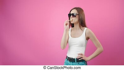 Front view of stylish young girl in trendy sunglasses posing in studio with lollipop. Attractive woman with dark hair licking sweet candy over pink background.