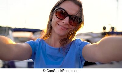 Woman in sunglasses makes selfie on the background of the marina with a lot of yachts and boats at sunset, close up. Slow motion
