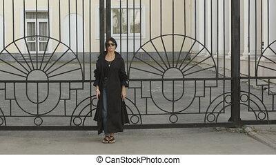 Woman in sunglasses near gate - Beautiful young woman in...