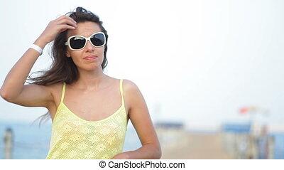 woman in sunglasses posing on the pontoon near sea