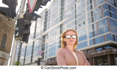 woman in sunglasses standing on a busy street. woman, a resident of the city.