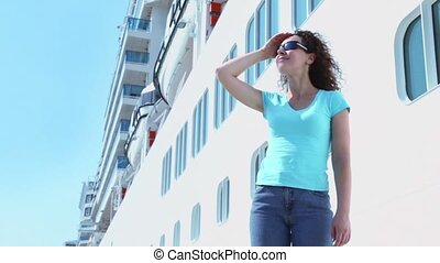 Woman in sunglasses stands and smiles near board of huge liner