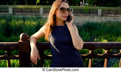 Woman in sunglasses talking on the smartphone outdoors at sunset