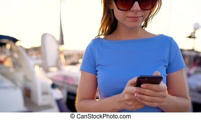 Woman in sunglasses talking on the smartphone while walking...