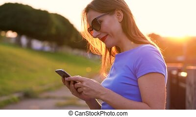 Woman in sunglasses using a smartphone outdoors at sunset -...