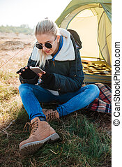Woman in sunglasses using phone while sitting at her tent