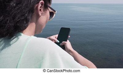 Woman In Sunglasses Using Smartphone Standing On Beach Near...