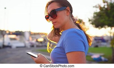 Woman in sunglasses using smartphone while walking down a...