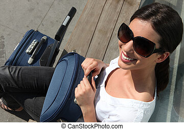 Woman in sunglasses waiting with a suitcase
