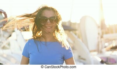 Woman in sunglasses walking along the dock with a lot of yachts and boats at sunset, close up. Slow motion
