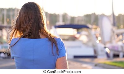 Woman in sunglasses walking along the dock with a lot of yachts and boats at sunset, close up