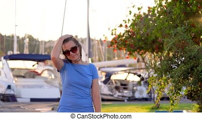 Woman in sunglasses walking along the dock with a lot of yachts and boats at sunset