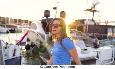Woman in sunglasses walking along the dock with a lot of...