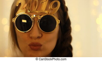 Woman in sunglasses with the number 2019 smiles in the New...