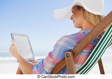 Woman in sunhat sitting on beach in deck chair using tablet ...