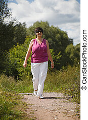 woman in sunny day on wood clearing goes at pathway, in sunglasses