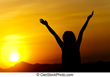 Woman in Sunset - Woman stretches her arms to sky and sun